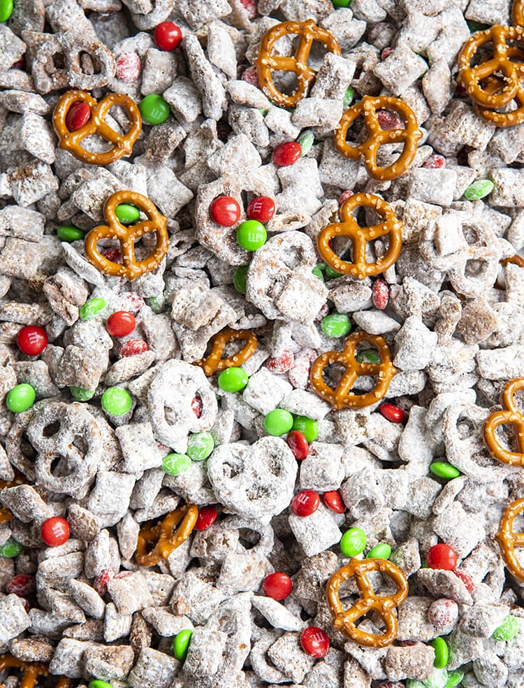 Christmas Muddy Buddies on a baking sheet lined with parchment paper. There are muddy buddies, red and green m&ms, and mini pretzels.