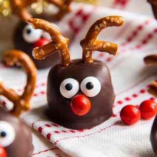 A cookie dough ball covered in chocolate, and decorated with pretzels, candy eyes and a red nose to look like a reindeer. On a white and red cloth.