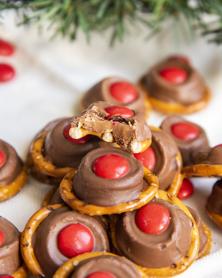 Rolo pretzel treats with a red m&m on top to look like Rudolph's nose. One is bitten into to show the chewy caramel in the middle.
