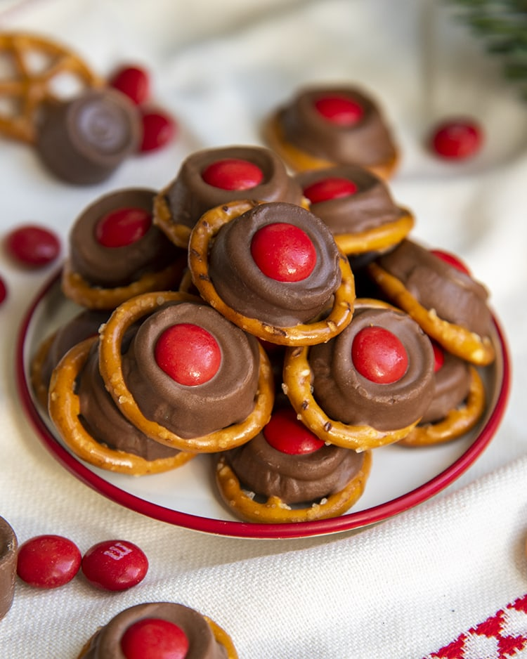 """A small plate full of """"rudolph noses"""" treats. Which are round pretzels topped with a slightly melted rolo, and a red m&m on top."""