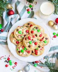 A plate of Christmassy chocolate chip cookies with red and green m&ms, perfect for Santa.