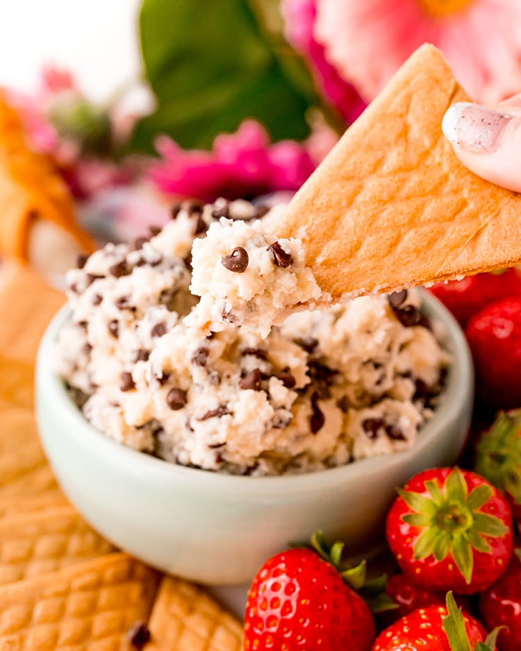 A bowl of cannoli dip sprinkled with mini chocolate chips, with a triangle shaped crepe cookie lifting some of the dip out of the bowl.