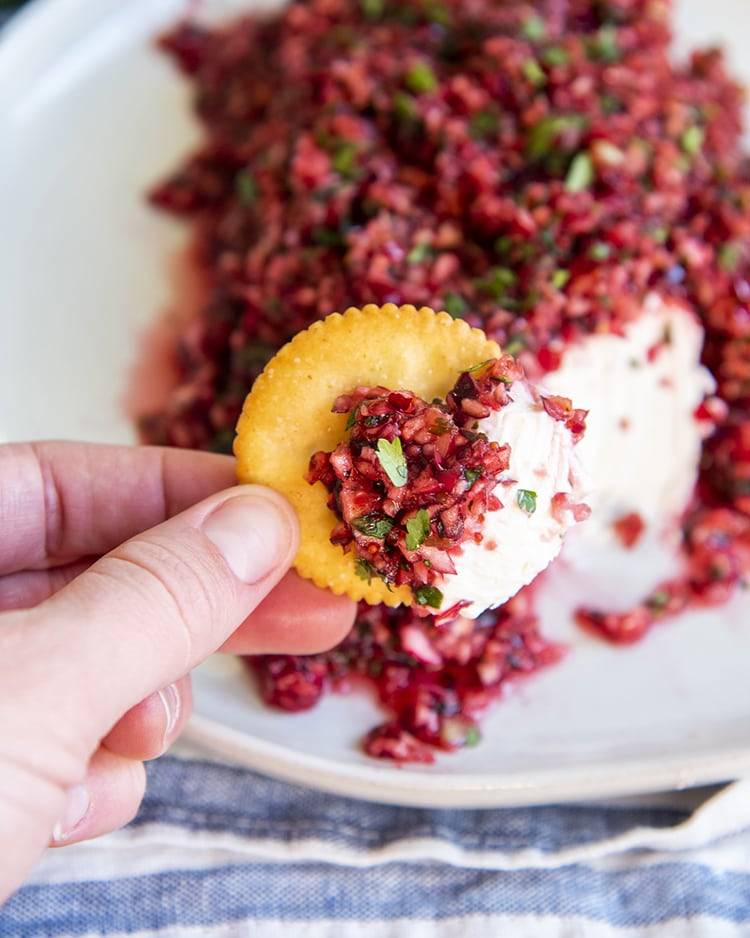 Cranberry salsa and cream cheese on a ritz cracker in front of a plate of cranberry salsa over a block of cream cheese.