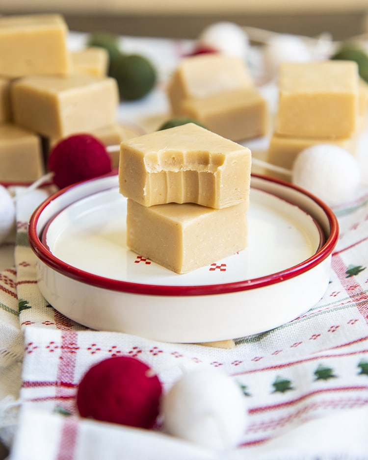 Two pieces of peanut butter fudge on a small white plate. The top piece has a bite taken out of it.