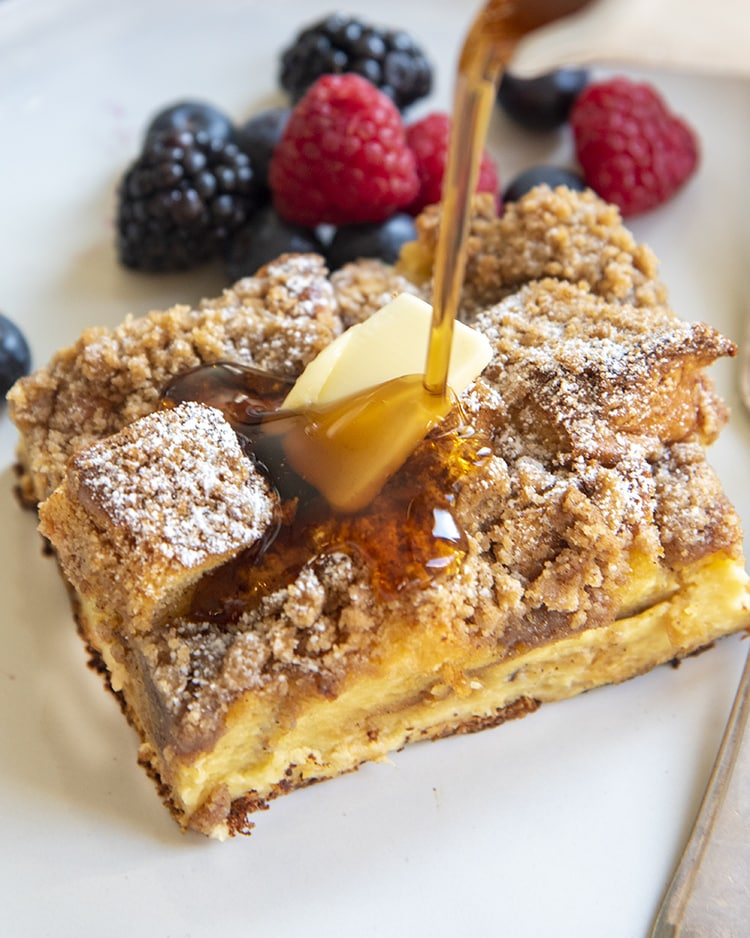A piece of overnight french toast casserole topped with berries and syrup is being poured over the top.