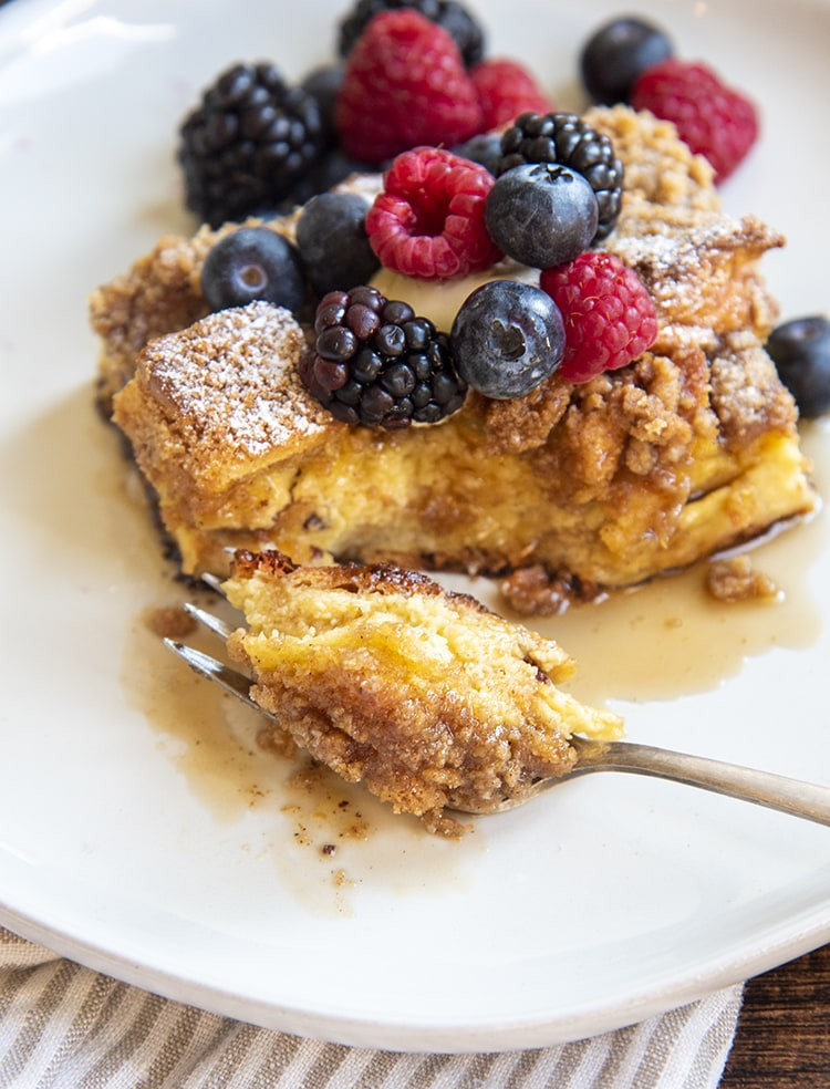 A piece of french toast casserole on a white plate, topped with fresh berries, and a fork cut a bite out of the piece.