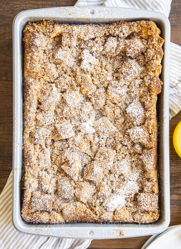 A pan of overnight french toast from above, with a crumb topping, and sprinkled with powdered sugar.