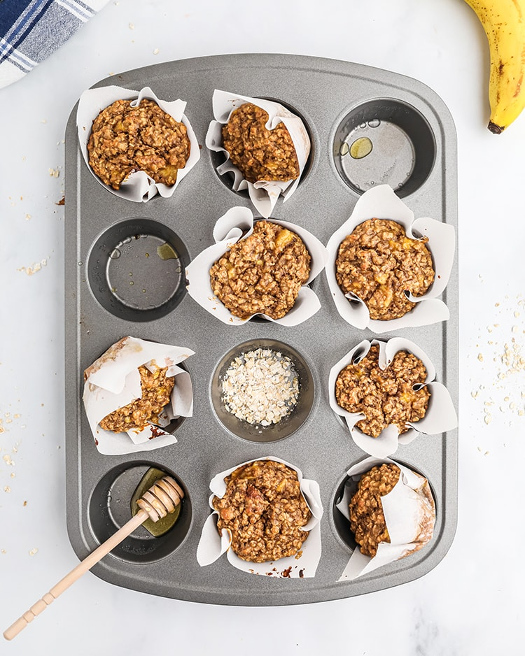 A muffin pan, with 8 muffins in it in white wrappers. The spots that are empty of muffins, one has a sprinkling of oats, others have a drop or two of honey.