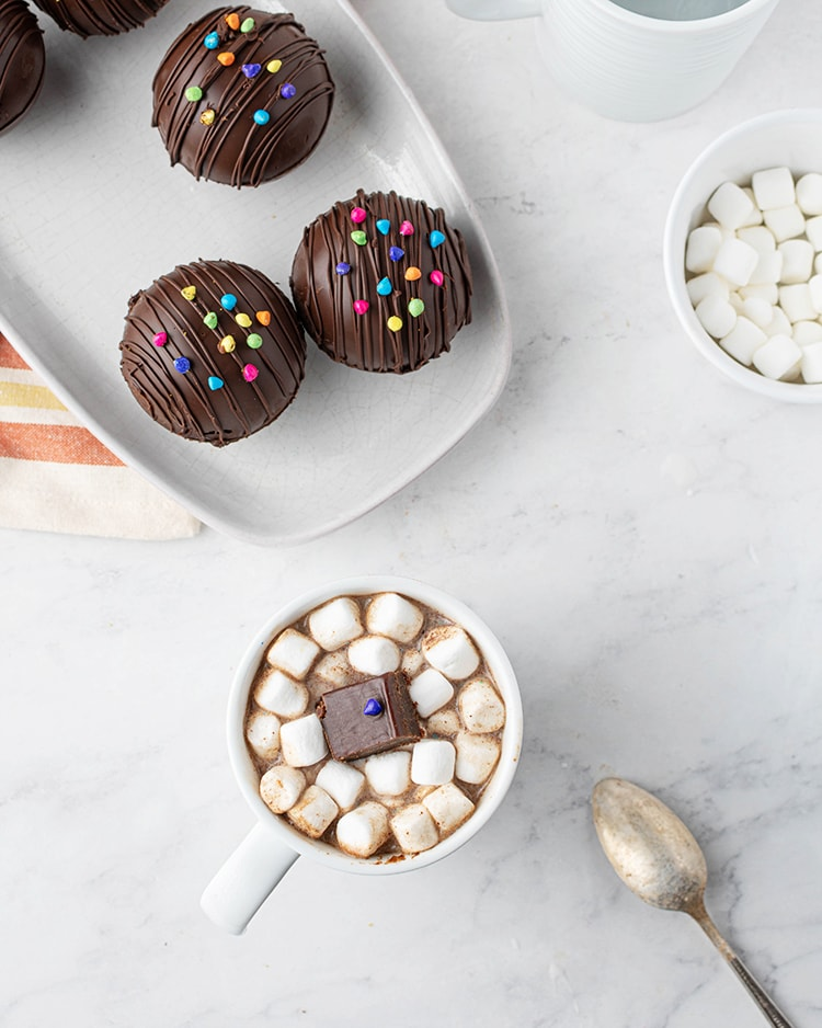 A white mug filled with hot cocoa, and mini marshmallows. A hand is holding a spoon in the mug, there is a small piece of a chocolate cosmic brownie on top of the marshmallows.