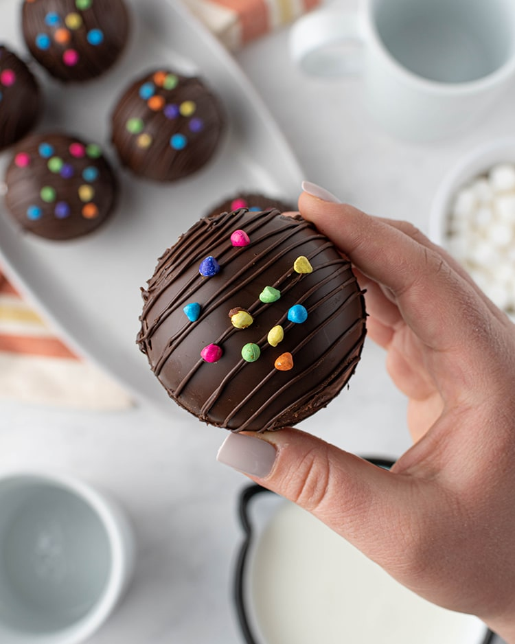 A hand holding a hot chocolate bomb, which just shows a chocolate ball, drizzled with chocolate on top and sprinkled with rainbow chips on top.