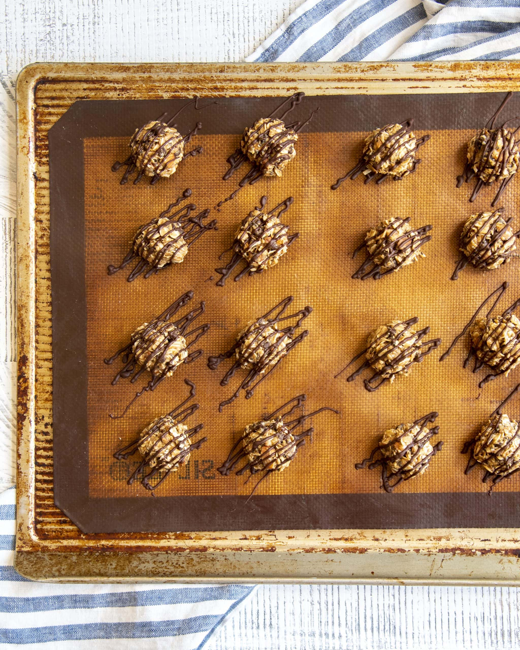 Almond joy energy bites on a baking pan, showing chocolate drizzled on the tops, and over drizzled on the sides.