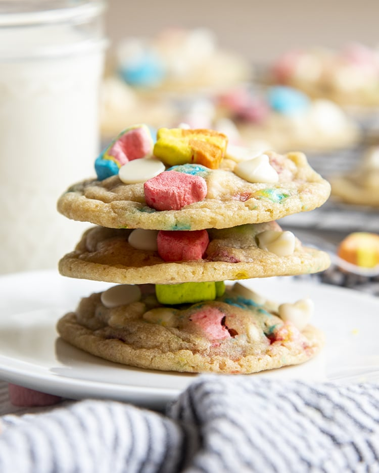 A stack of three lucky charms cookies on a small white plate. Each cookie is topped with the marshmallows from lucky charms cereal.