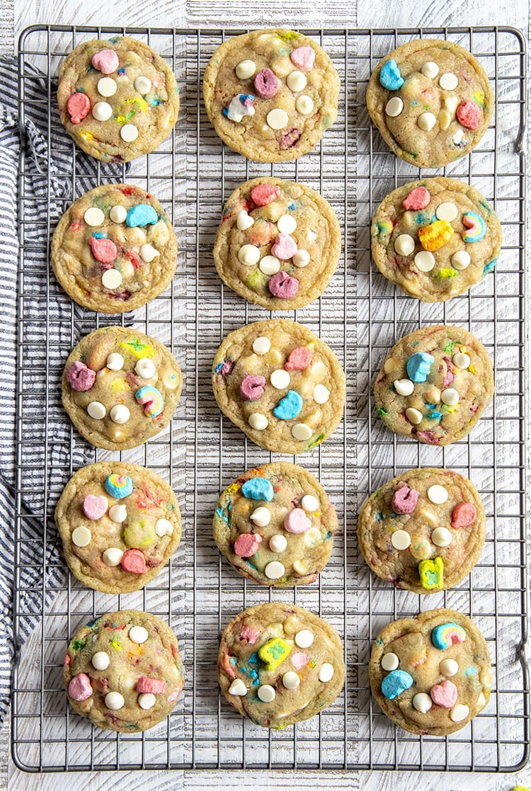 Fifteen lucky charms and white chocolate chip cookies on a cooling rack. The cookies are filled with the marshmallows in lucky charms cereal and white chocolate chips, and you can see a few of each on top of all the cookies.