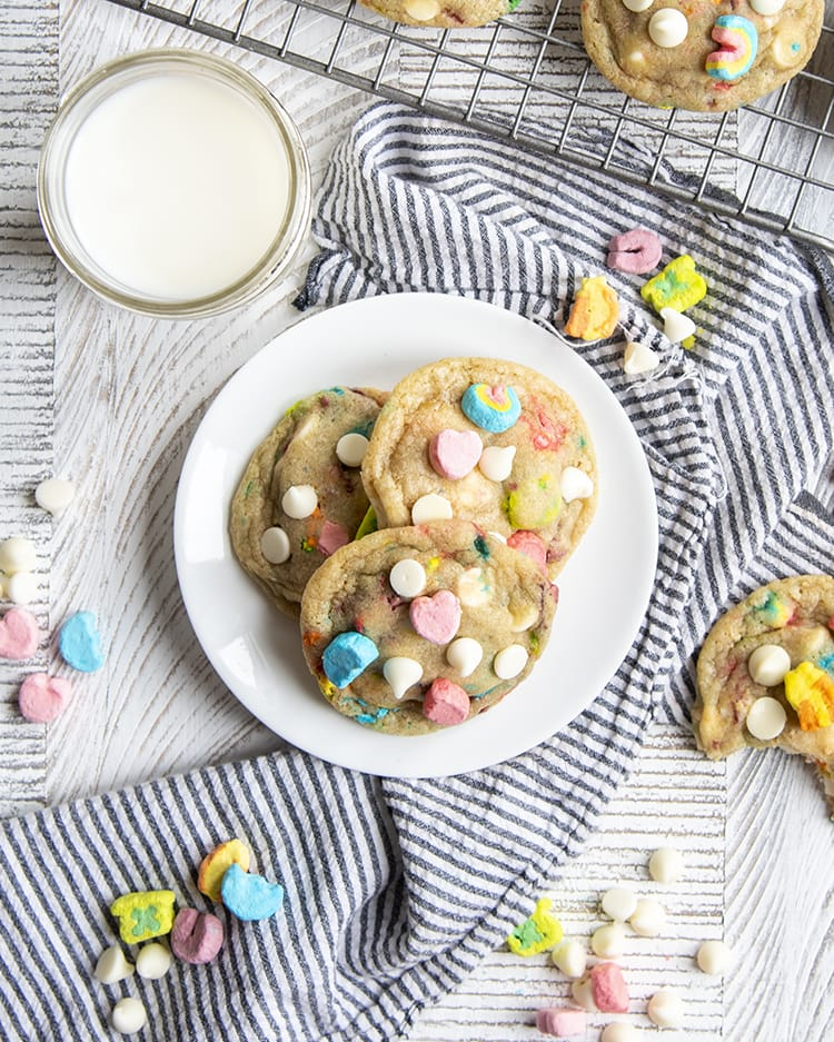 The lucky charms cookies on a small white plate with a glass of milk behind. On top of the cookies there are lucky charms marshmallows, and white chocolate chips. There are more marshmallows and chocolate chips around the plate.