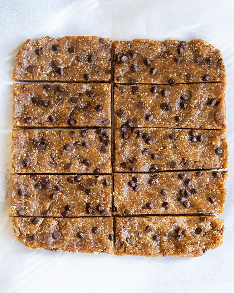 A few homemade peanut butter chocolate chip larabars still in the shape of a square pan they were in, removed from the pan and placed on parchment, and cut into 10 rectangular pieces.