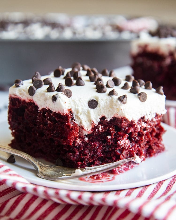 A square piece of red cake topped with a white cream cheese frosting, and topped with mini chocolate chips. There is a bite out of the cake and a fork laying along side it.