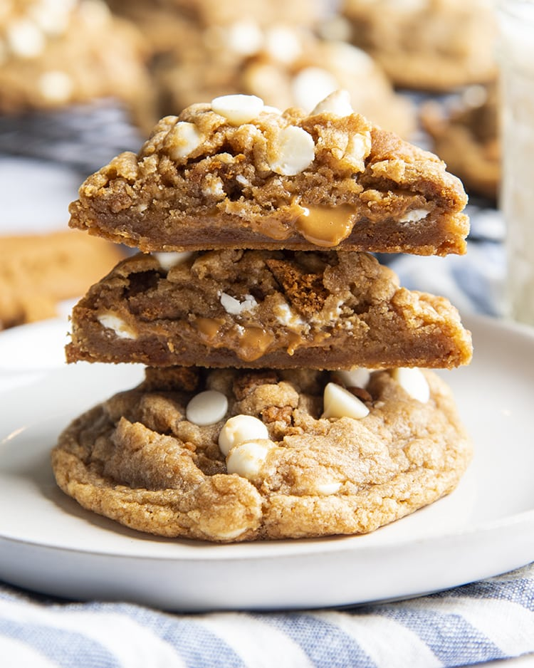 A giant cookie on a small plate with another cookie cut in half and stacked on top, showing the middle of the cookie, with white chocolate chips, and melty cookie butter spread oozing out of the middle.
