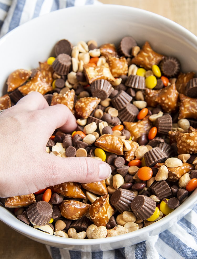 A hand reaching in to a bowl of a chocolate peanut butter snack mix.