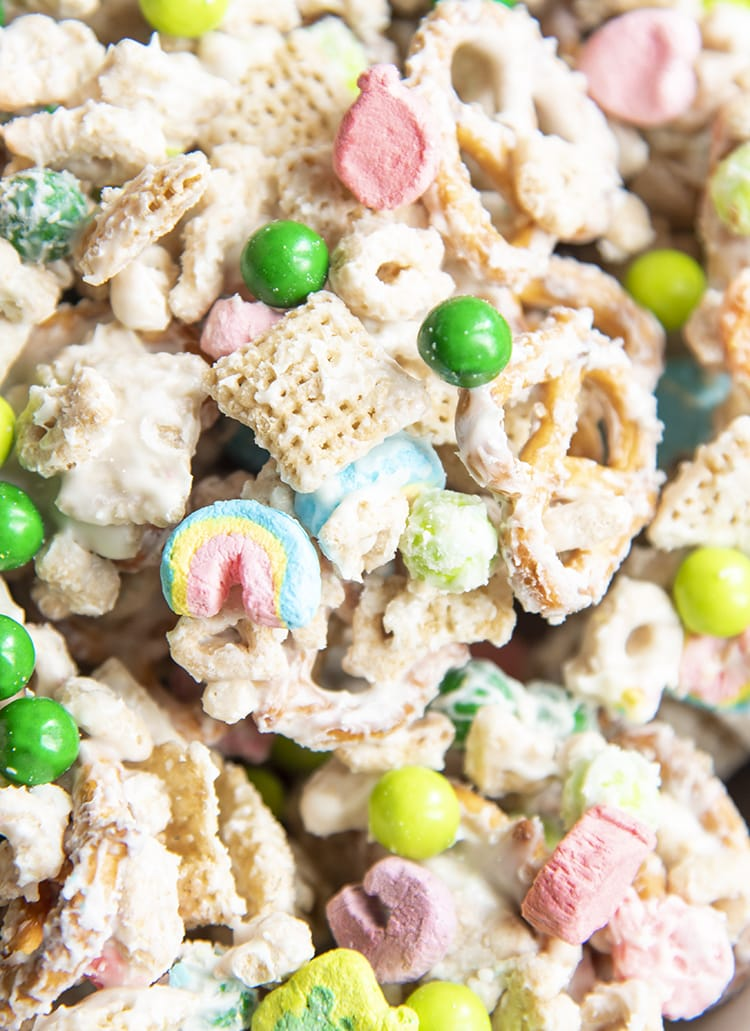 A close up of a snack mix with chex, pretzels, lucky charms, and green chocolate candies, all covered in white chocolate.