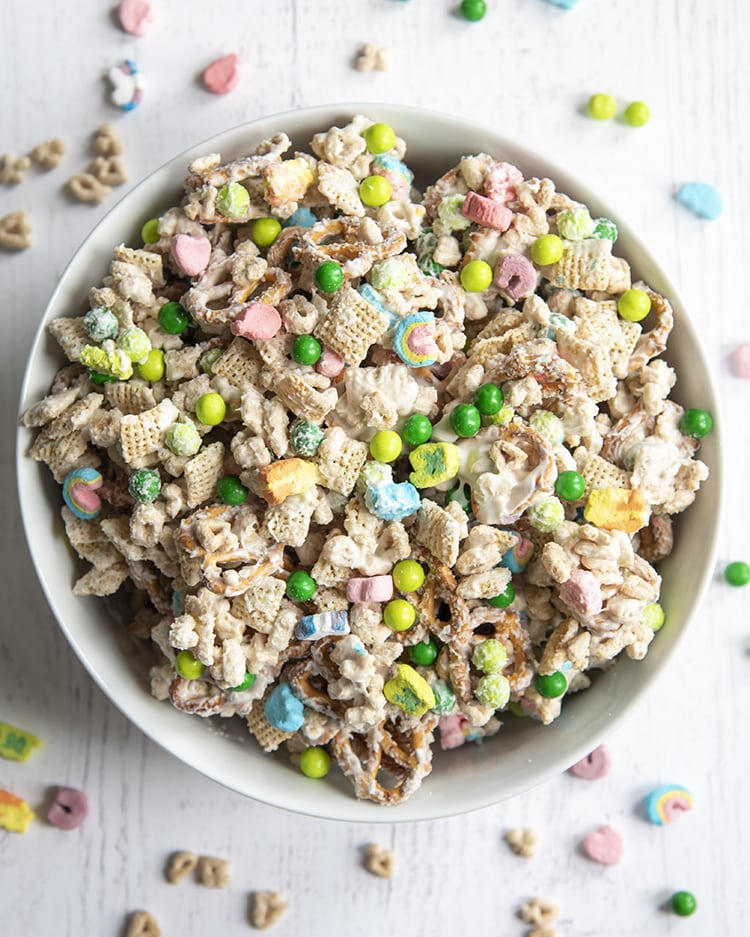 A bowl of a lucky charms snack mix, with cereal, marshmallows, and green chocolate candies covered in melted white chocolate.