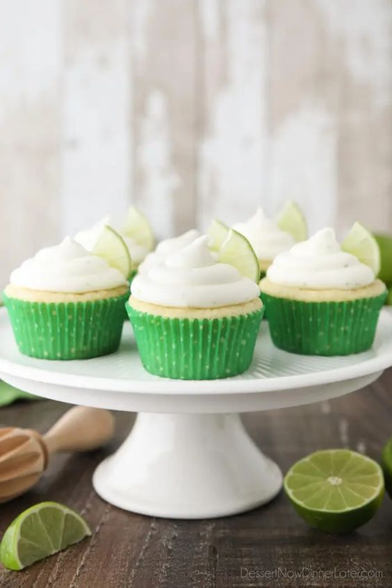 Cupcakes on a cake stand with green cupcake liners, and piled with a white frosting on top, and a lime slice on each.