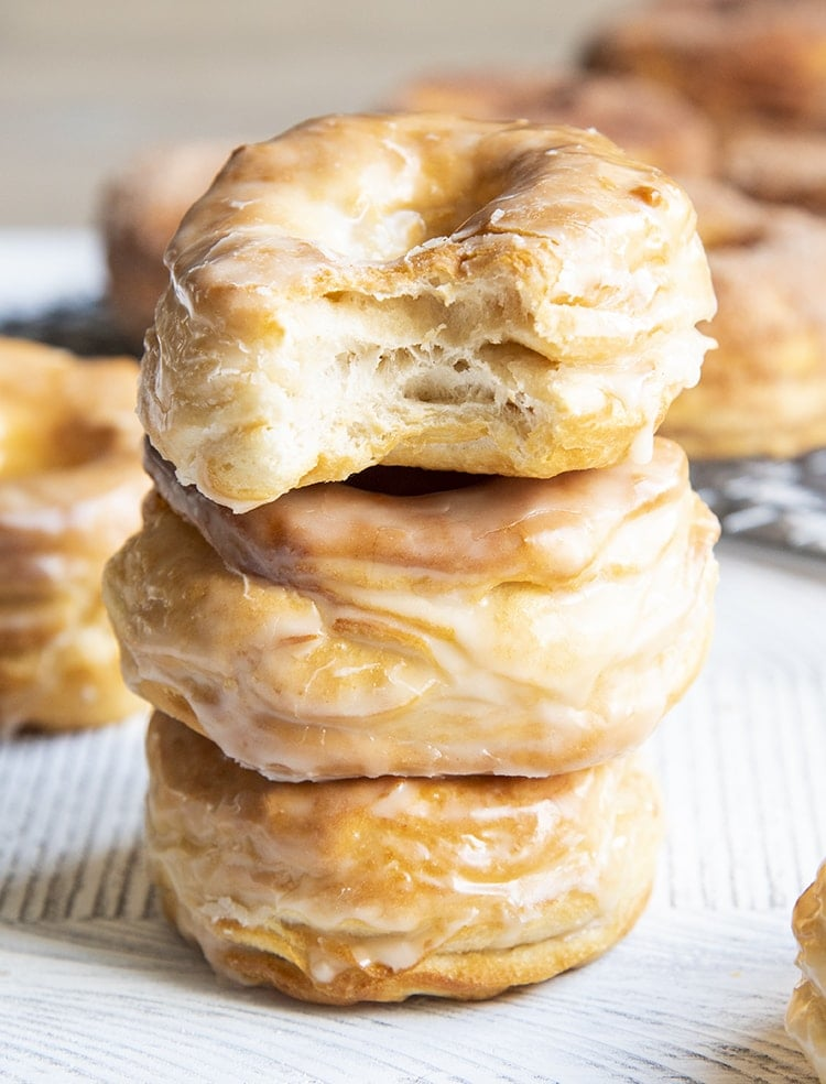 A stack of three air fryer donuts covered in a vanilla glaze. The top donut has a bite out of it showing flaky layers.