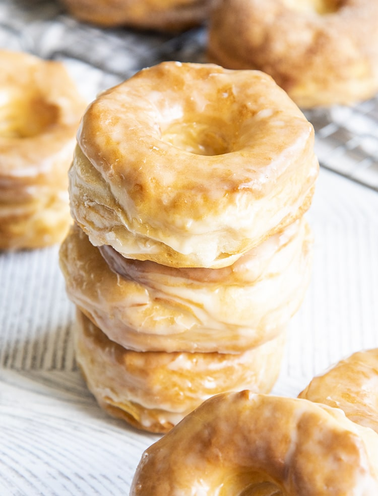 A stack of three air fryer donuts covered in a vanilla glaze.