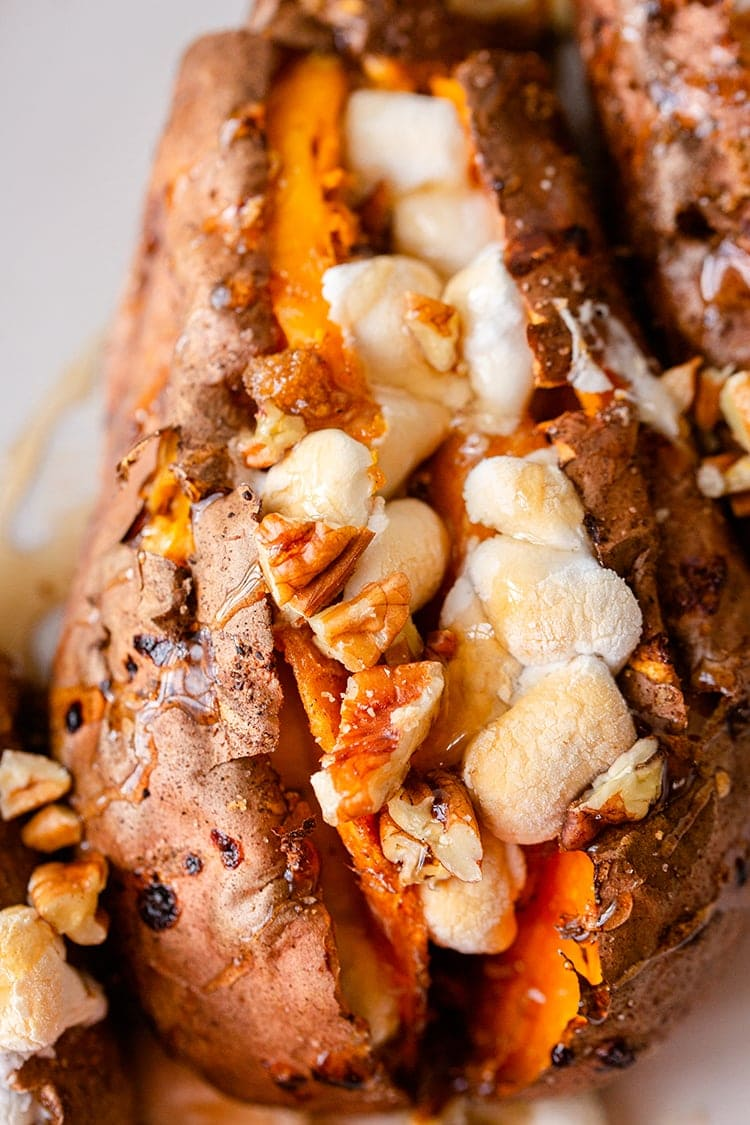 A close up of a baked sweet potato full of brown sugar, toasted marshmallows and pecans, with maple syrup drizzled over the top.