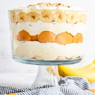 A layered banana pudding trifle in a trifle dish, with layers of Nilla Wafers, Banana Slices, Vanilla Pudding, and Whipped Cream.