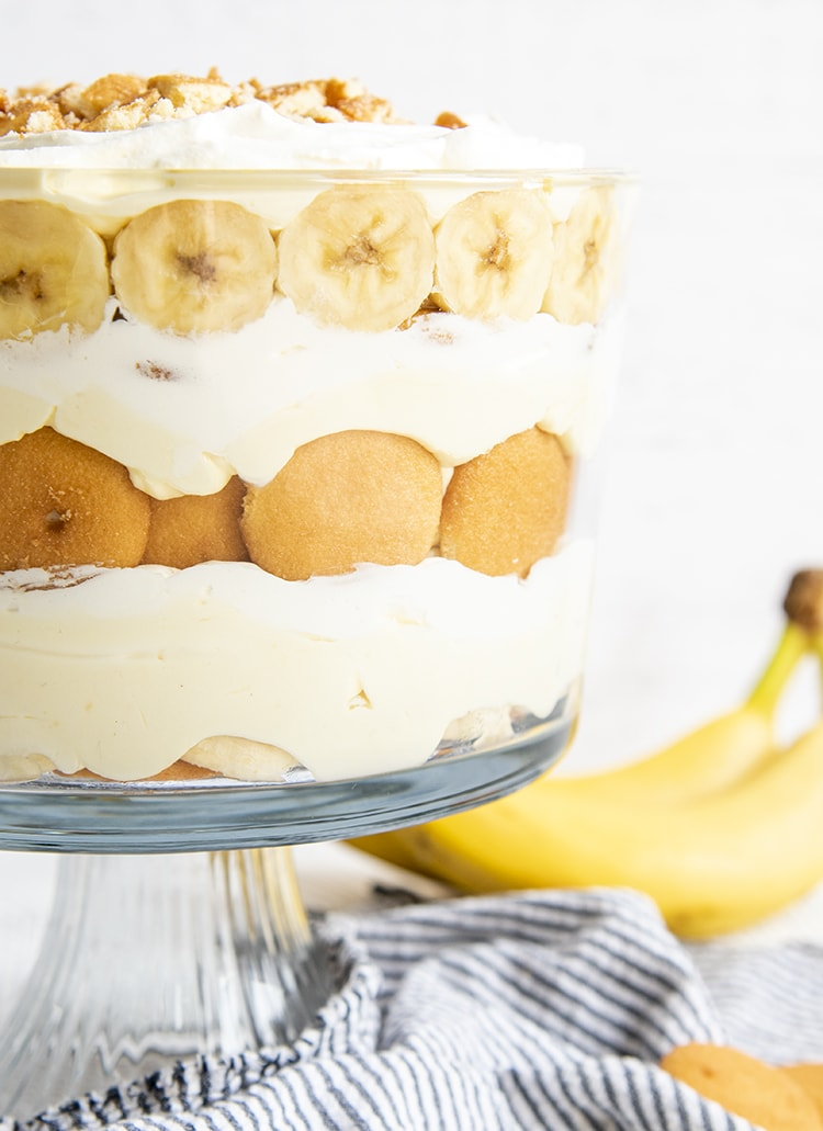 A close up of a layered banana pudding trifle in a trifle dish, with layers of Nilla Wafers, Banana Slices, Vanilla Pudding, and Whipped Cream.
