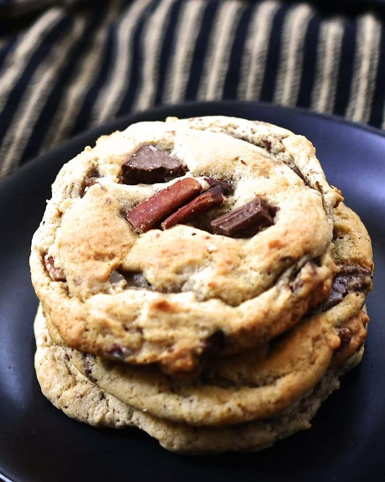 A close up of a stack of cookies on a black plate. The cookie has nuts and chocolate chunks in it.