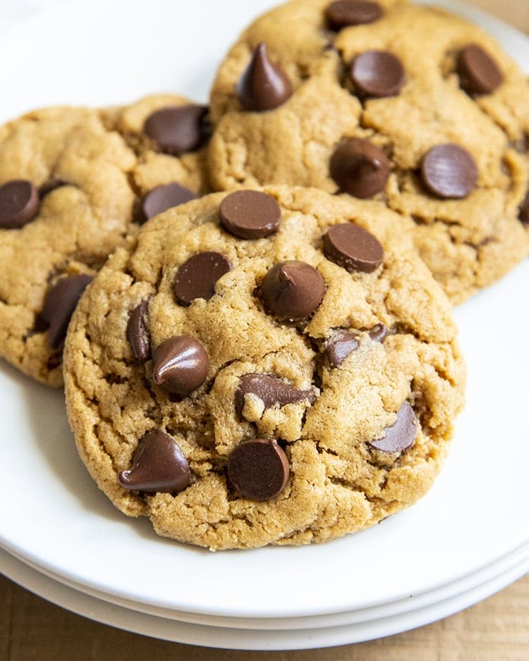 A close up on a peanut butter chocolate chip cookie on a plate, with two cookies behind it.