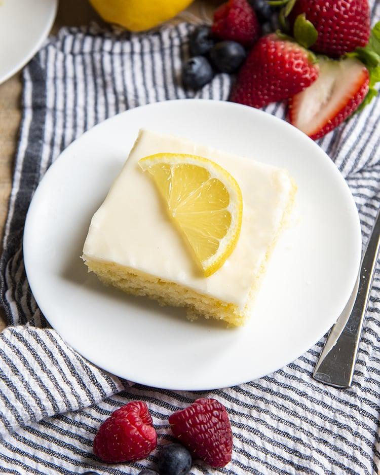 An overhead shot of a slice of lemon sheet cake on a white plate topped with a lemon slice.
