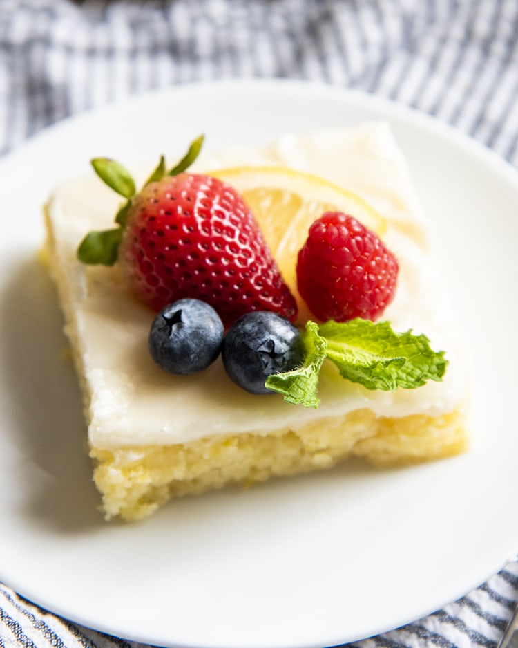 A slice of lemon sheet cake on a plate topped with fresh berries and mint leaves.