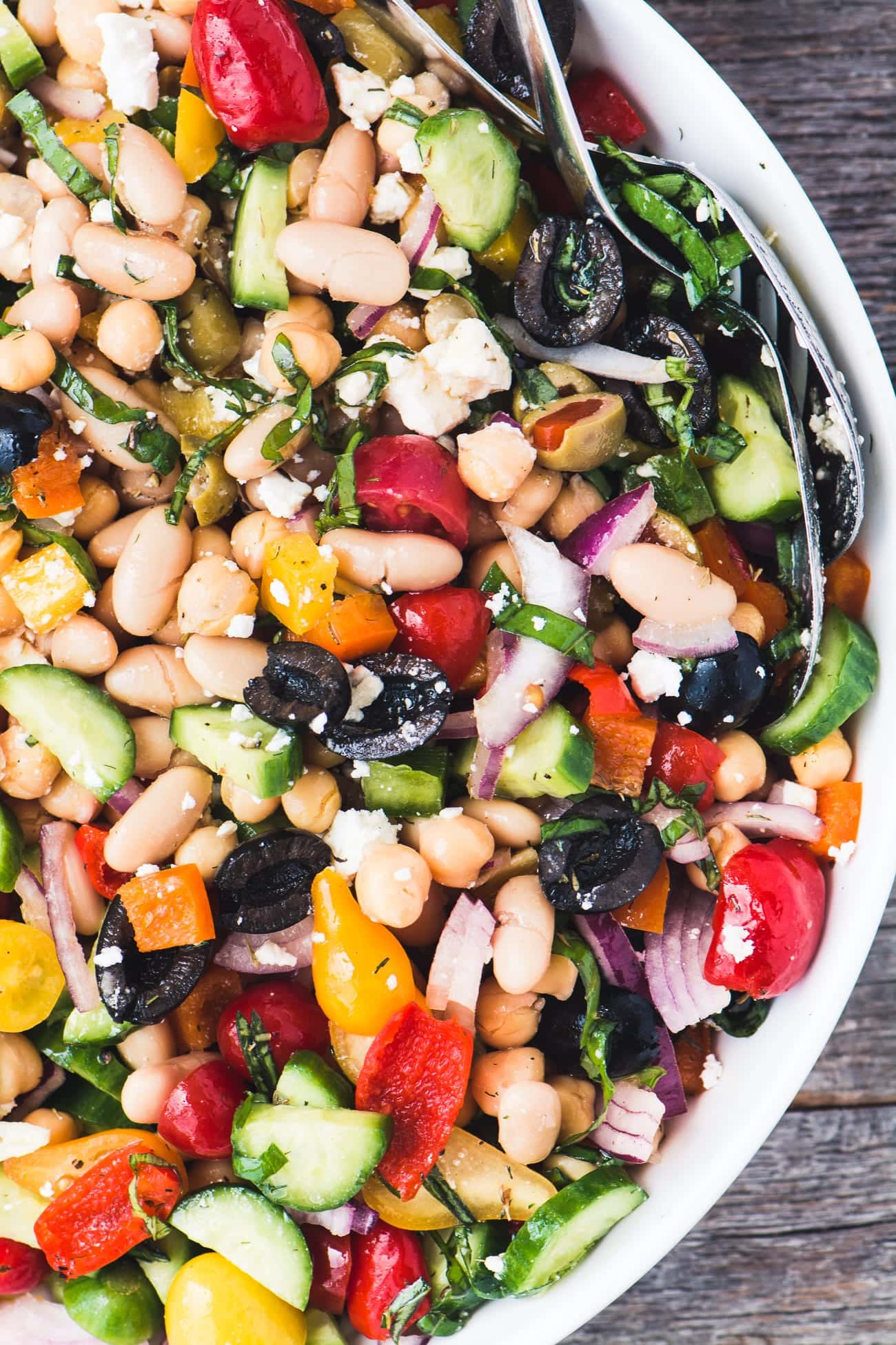 A delicious bean salad in a white bowl full of tomatoes, peppers, red onion, olives, and cheese.