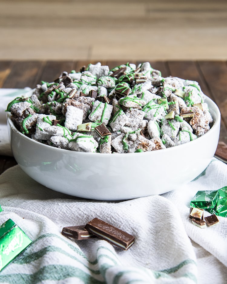 Mint Chocolate Muddy Buddies in a white bowl. They are drizzled with green candy melts over the top.