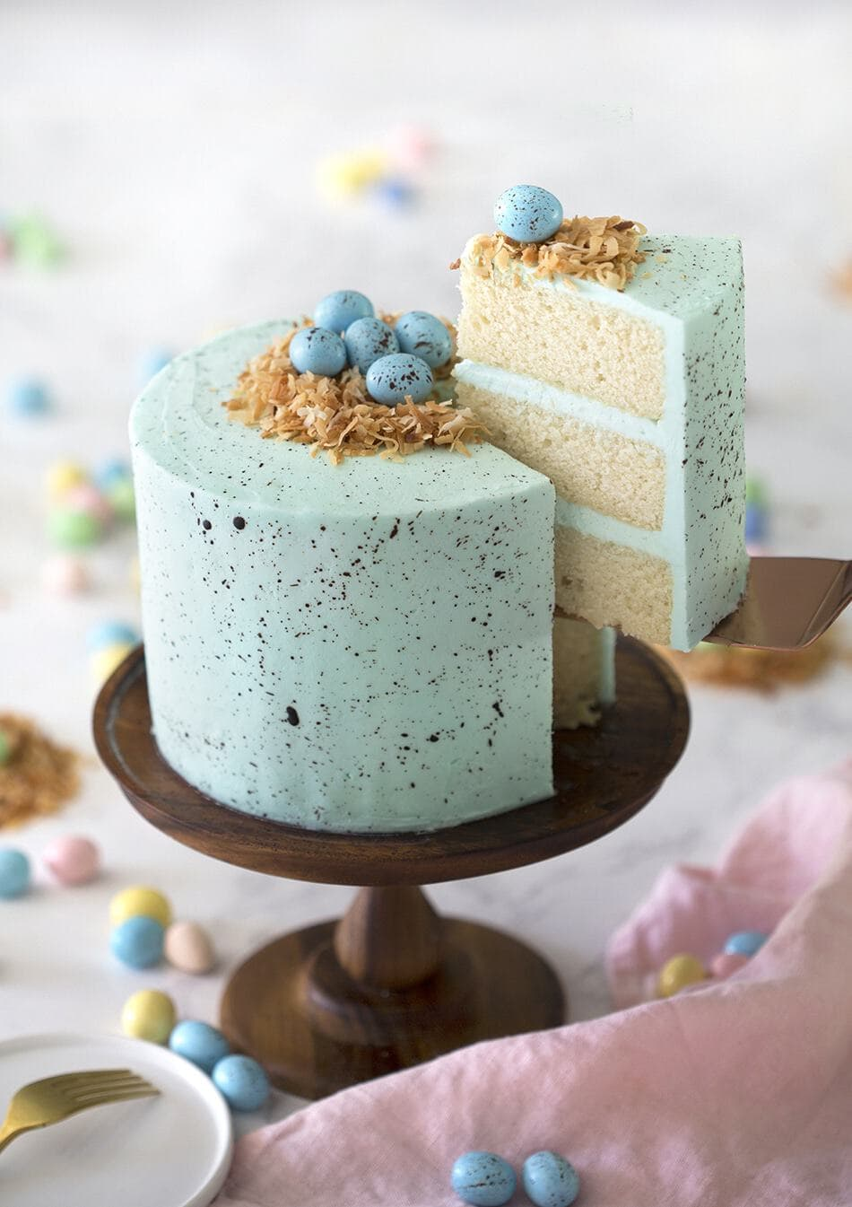 A three layered white cake, with a blue speckled frosting, topped with toasted coconut and blue candied eggs on top.