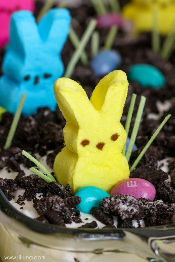 A pudding dessert in a baking pan topped with crumbles of Oreos, and a bunny Peep candy.