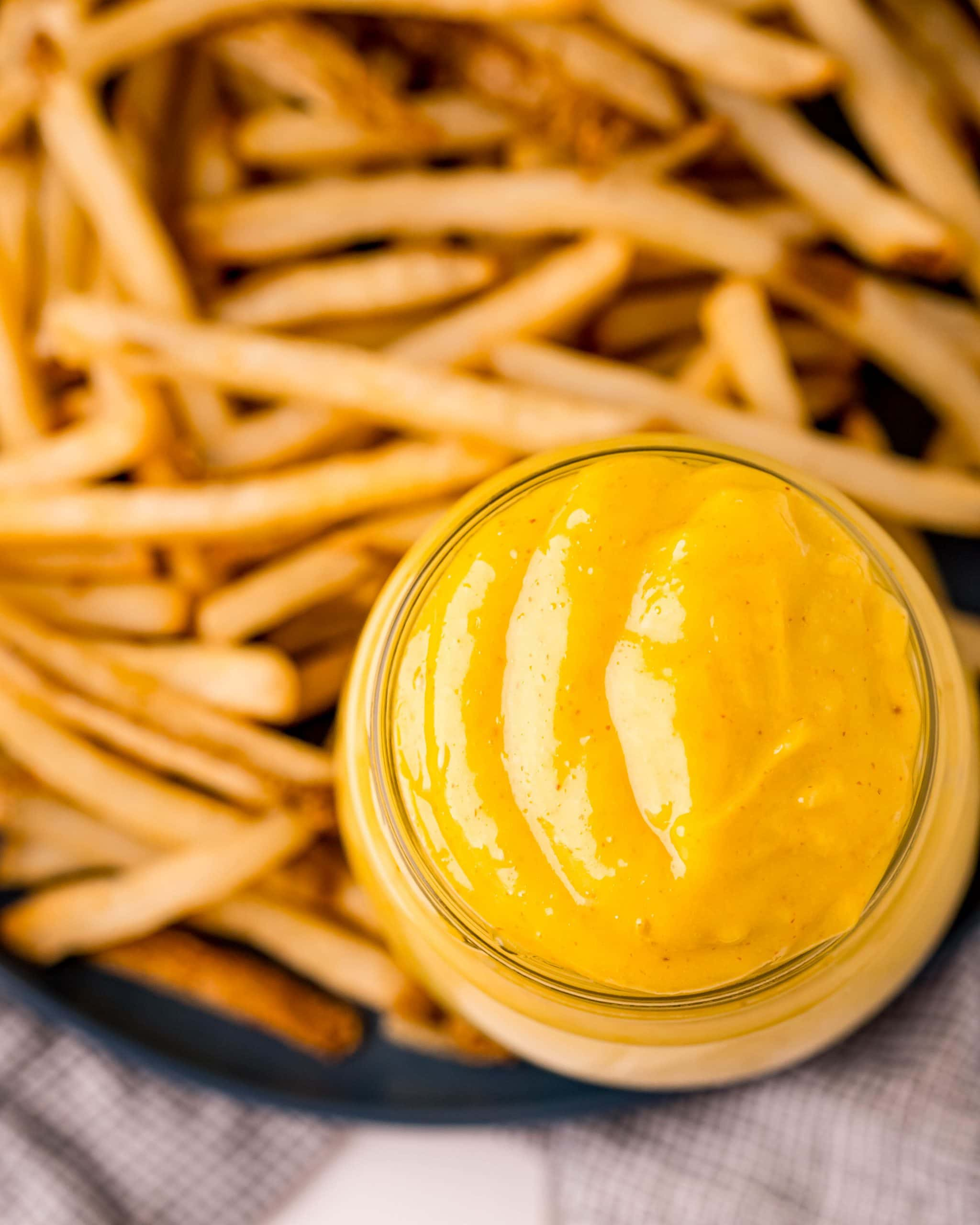 An overhead shot of a jar full of a yellow, creamy mixture that is a homemade aioli, that is also on a plate with a bunch of french fries.