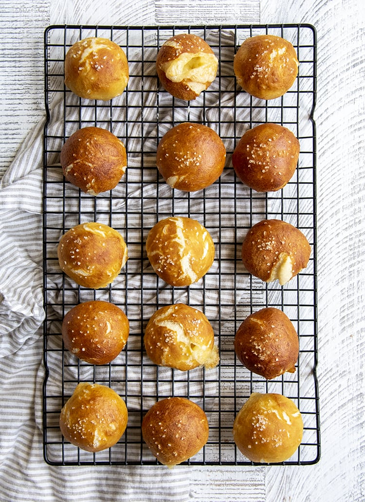 Soft pretzel balls on a cooking rack, they are a nice golden brown color with a couple cracks, and sprinkled with coarse salt on top.