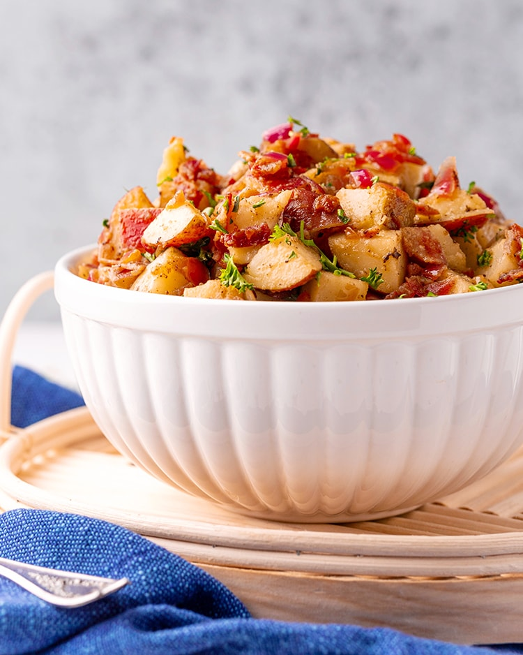 A side shot of a white bowl holding a red potato salad in the bowl, the salad is heaping over the top of the bowl.