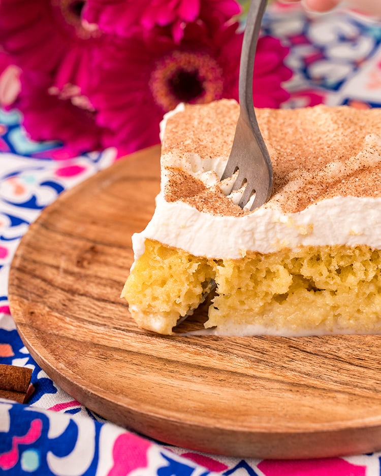 A piece of tres leches cake on a wooden plate, with a fork cutting a bite out of it.