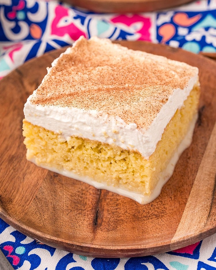 A piece of tres leches cake on a wooden plate. You can see the milks coming out the bottom, the whipped cream on top is sprinkled with cinnamon sugar.