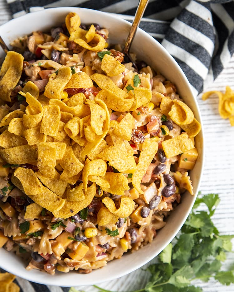 A bowl of BBQ chicken pasta salad, you can see mini farfalle, red onion, black beans, bell pepper, corn, and cilantro all in a creamy sauce. Topped with corn fritos!