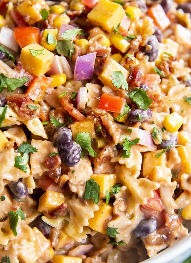 A close up of BBQ chicken pasta salad, you can see mini farfalle, red onion, black beans, bell pepper, corn, and cilantro all in a creamy sauce.