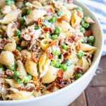 A shot of half of a white bowl full of a creamy pasta salad with shell noodles, bacon, and peas in a white creamy sauce.