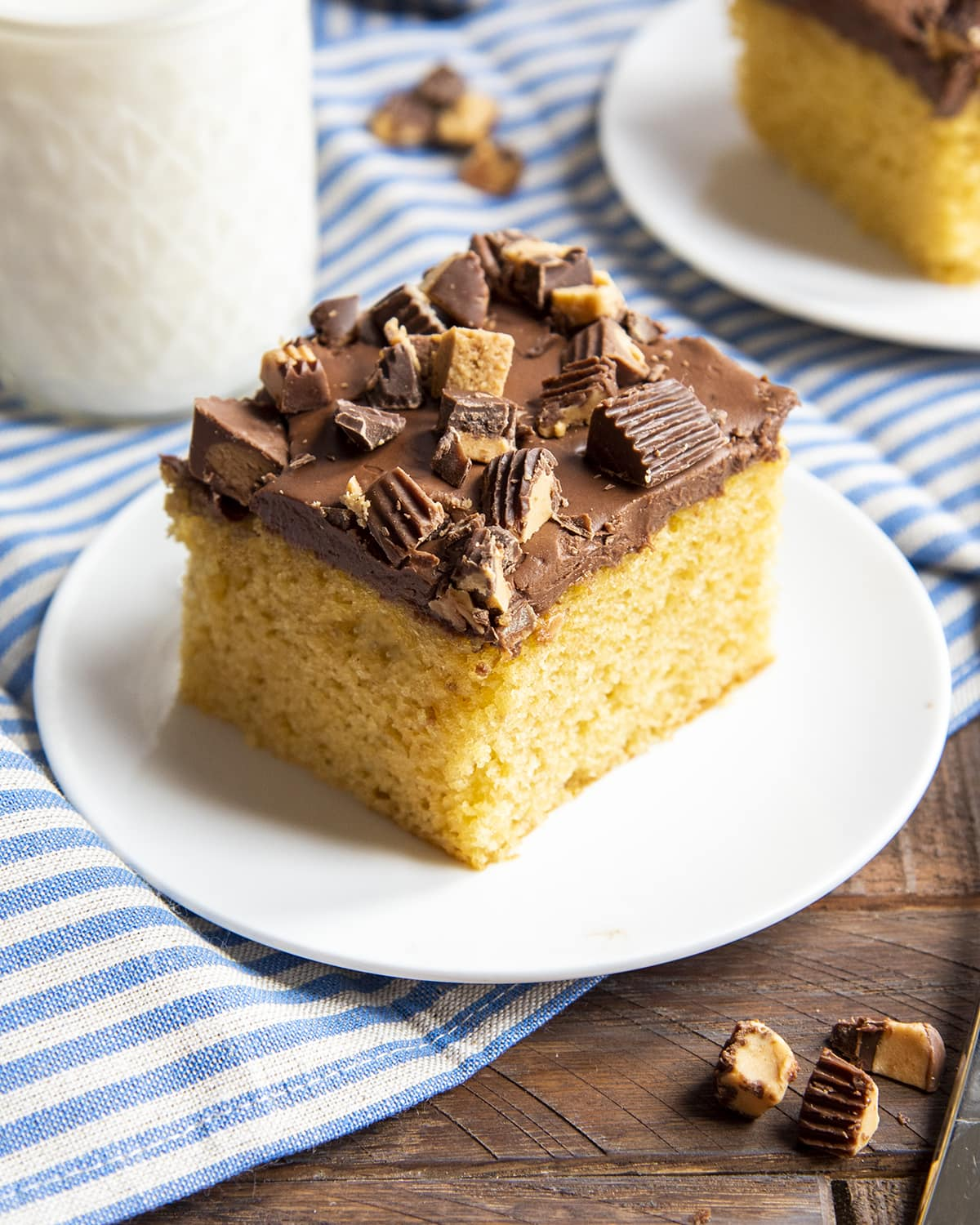 A piece of peanut butter cake made with a cake mix topped with chocolate frosting and peanut butter cups.
