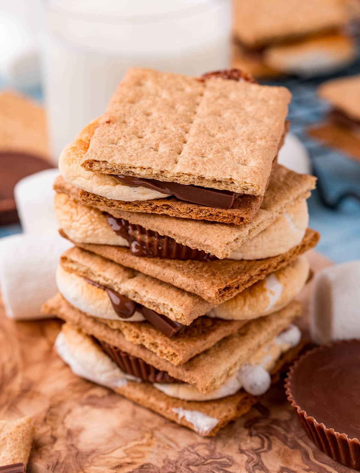 A stack of 4 s'mores on top of each other on a wooden board.