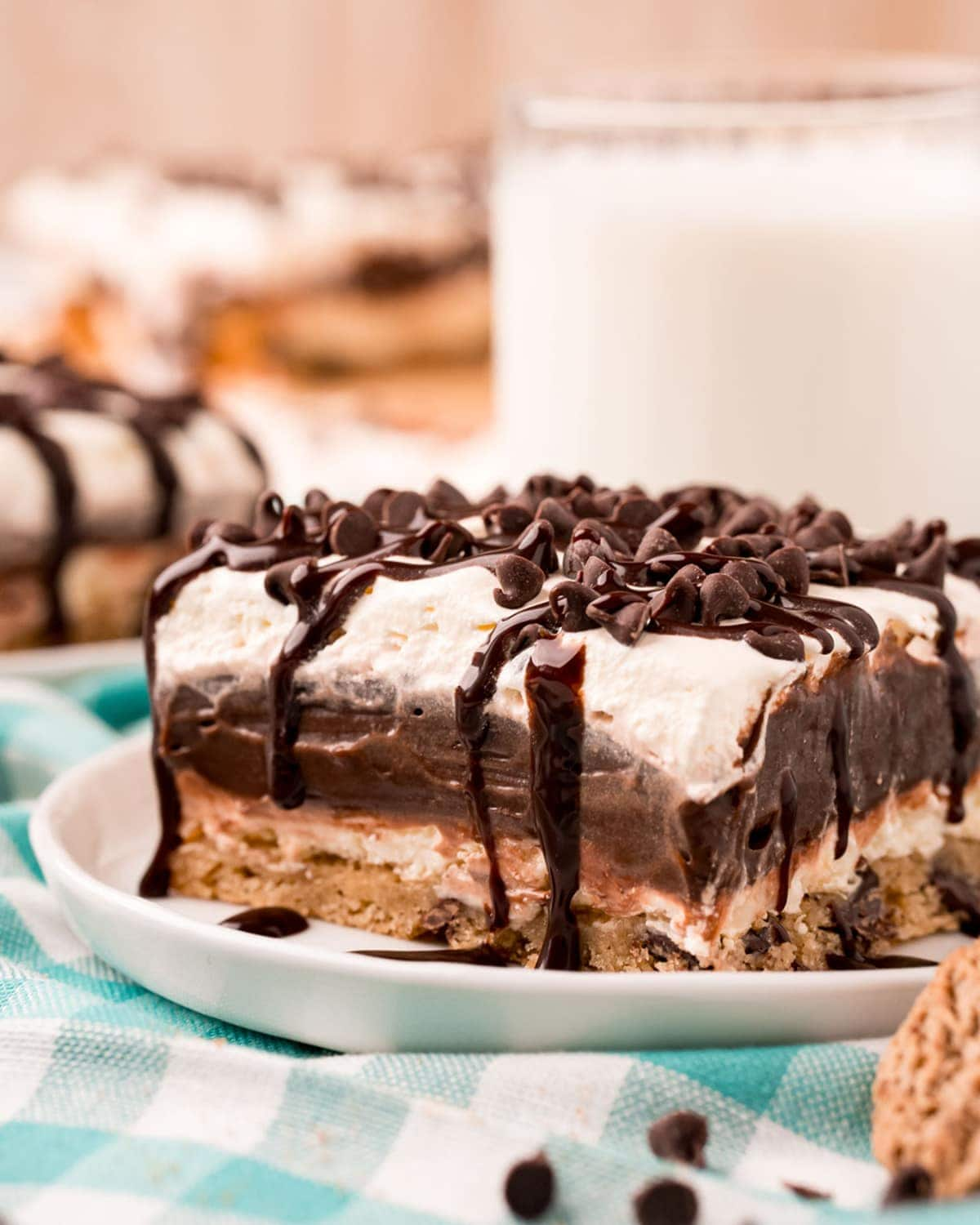 A piece of layered chocolate hip cookie delight on a small plate, topped with mini chocolate chips, and drizzled with chocolate syrup.