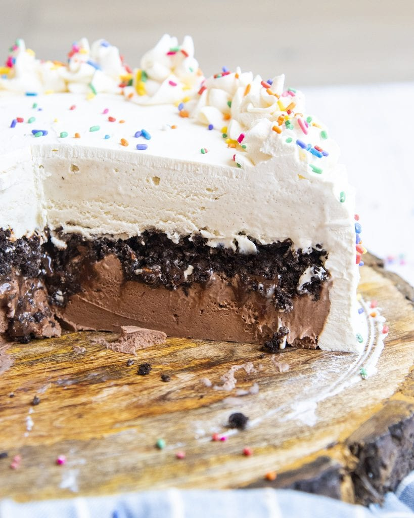 An ice cream cake on a wooden board, cut open to reveal the inside of the cake with chocolate ice cream, oreo crumbs, and vanilla ice cream on top.